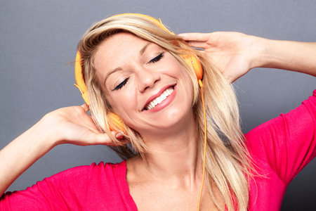 flashy: gorgeous young blond woman with flashy pink sweater relaxing in listening to music on headphones, grey background studio