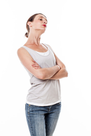 sulking: attitude concept - sulking young woman with arms folded posing with chin up for arrogance or statement, gray background studio Stock Photo