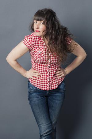 arrogancia: actitud concepto - mujer joven atractiva con el pelo muy largo que se inclina hacia delante con las manos en las caderas para posar en la crianza de los hombros, fondo gris estudio