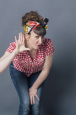 louder: communication problem - deaf-like retro style woman leaning forward with hand on ear to understand louder,gray background studio Stock Photo