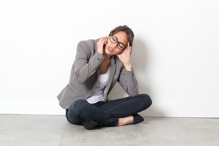 phone professional: professional anxiety - annoyed young executive woman talking on her cell phone with a headache, sitting alone on the office floor over sparse white background Stock Photo
