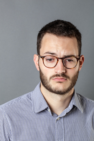 emptiness: feeling depressed - portrait of a disappointed young man with beard and eyeglasses expressing emptiness and disillusion, grey background studio