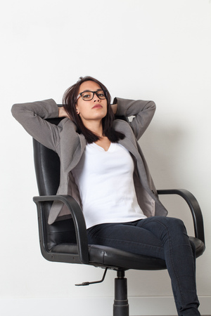 company person: female self-employment - cool beautiful young corporate woman relaxing in an office chair resting or expressing laziness over sparse white background