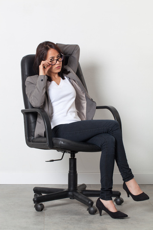 business skeptical: female self-employment - skeptical beautiful young corporate woman sitting in an office chair for her startup job over sparse white background