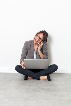 homeoffice: home-office startup - happy beautiful multi-ethnic young woman working on her laptop, talking on the phone,sitting on the floor over sparse white background