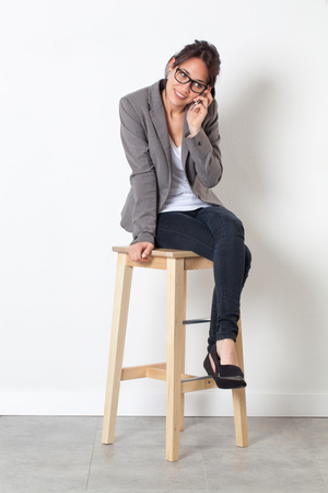 sparse: professional communication - smiling young corporate woman working with her cell phone, sitting on a stool over sparse white background