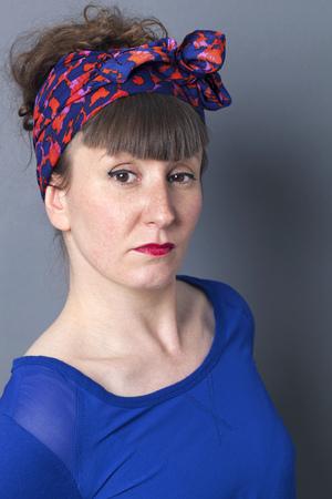arrogancia: orgullo y la arrogancia - sorprendieron a la mujer del estilo retro expresarse con actitud, fondo gris estudio Foto de archivo