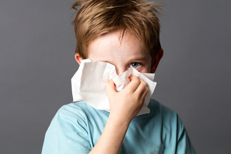 holding nose: healthcare learning - cute little child with red hair and blue eyes hiding with a tissue to clean his nose from a cold or having hay fever, grey background studio Stock Photo