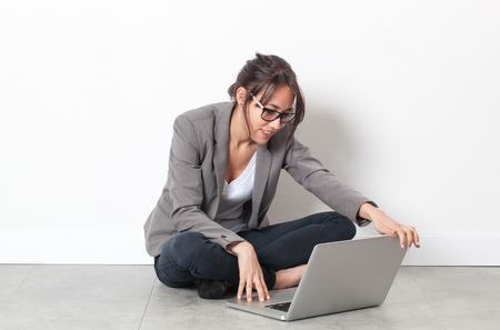 homeoffice: home-office startup - smiling multi-ethnic young woman working on her computer, sitting crossed legs on the floor over sparse white background