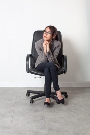 business skeptical: female self-employment - serious beautiful young businesswoman sitting in an office chair for her first job over sparse white background