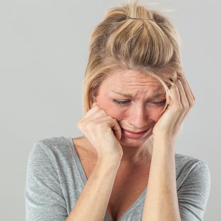 in tears: concepto de teatro - deprimido joven rubia en el dolor con grandes lágrimas expresando su pesar y tristeza, fondo gris estudio