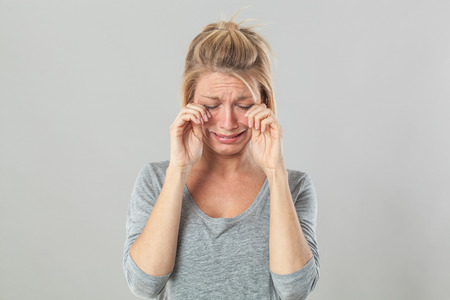 disappointed: drama concept - complaining young blond woman crying with big tears expressing sadness and disappointment, grey background studio Stock Photo