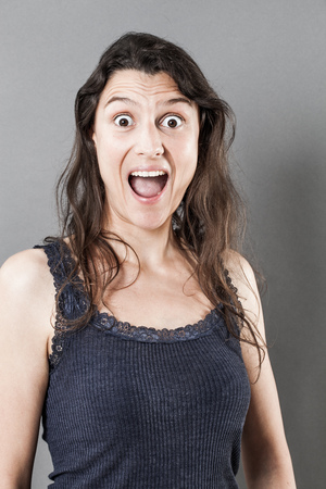 eyes opened: surprise concept - stunned young woman with long fine hair, mouth and eyes wide opened expressing amazement, grey background studio