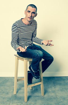 expresivo lenguaje corporal - infeliz joven con el pelo corto hablando con las manos sentado solo en un taburete, efectos verdes