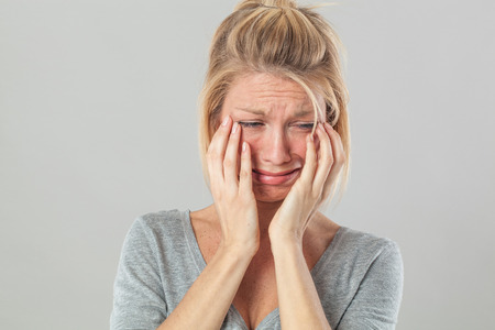 lagrimas: concepto de teatro - mujer joven rubia infantil llorando con grandes lágrimas que expresa su dolor y pesar, fondo gris estudio