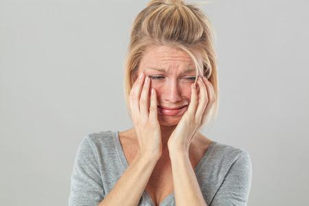 lacrime: concetto di dramma - infantile giovane donna bionda che grida con grosse lacrime che esprime il suo dolore e rimpianto, sfondo grigio studio