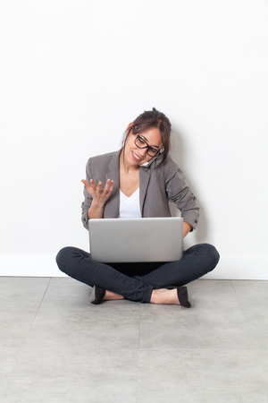 homeoffice: home-office startup - beautiful multi-ethnic young woman working on her laptop, talking on the phone, sitting on the floor over sparse white background Stock Photo