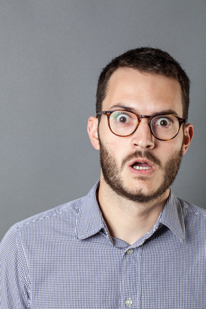 consternation: surprise concept - unhappy young bearded businessman with eyeglasses expressing amazement and fear, grey background studio