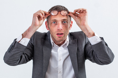 stunned: surprise concept - stunned 40s entrepreneur holding his eyeglasses on the forehead, finding a great idea or perspective to his business, grey background studio