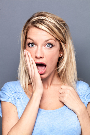 outraged: surprise concept - outraged sexy young blond woman with blue eyes wide and mouth opened expressing mistake or regret, grey background studio