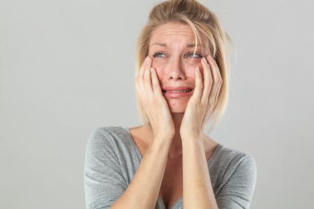 ドラマ コンセプト - 彼女の失望と悲しみ、灰色の背景のスタジオを表現する大きな涙を痛みで若い金髪女性が泣いています。