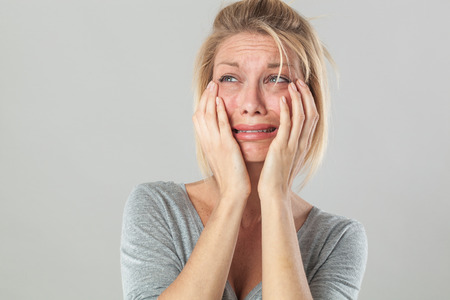 drama concept - crying young blond woman in pain with big tears expressing her disappointment and sadness, grey background studio Archivio Fotografico