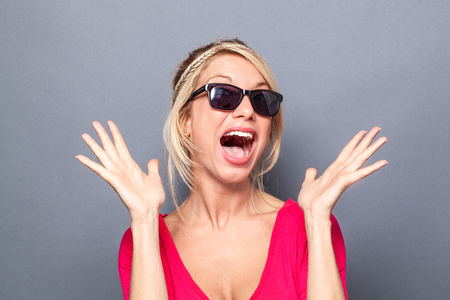 extrovert: surprise concept - bubbly young blond woman looking like a star with her sunglasses, using both hands and facial expression for surprise and happiness, grey background studio Stock Photo