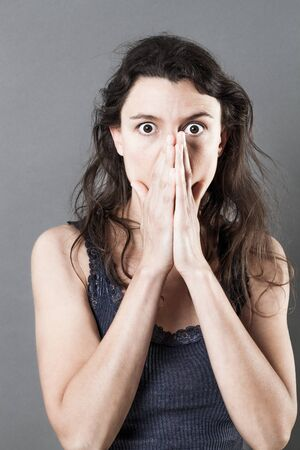 consternation: confusion concept - stressed out young woman hiding her mouth for mistake or consternation, grey background studio Stock Photo
