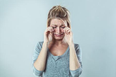 ドラマ コンセプト - 失敗と失望、灰色の背景のスタジオ、コントラスト効果を表現する大きな涙を泣いている悲観的な若いブロンド女性