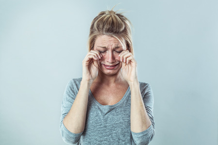 lagrimas: concepto de teatro - mujer joven rubia sombrío llorando con grandes lágrimas que expresa el fracaso y la decepción, el estudio de fondo gris, contrastar los efectos