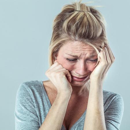 drame concept - déprimé jeune femme blonde dans la douleur avec de grosses larmes exprimant son échec et de tristesse, gris studio de fond, contraste effets