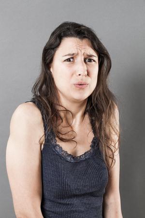 mujer decepcionada: retrato de miedo - el sufrimiento mujer joven con el pelo bien largo expresando su decepción, ansiedad y preocupación, estudio sombrío fondo gris