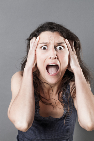 consternation: portrait of fear - screaming young woman panicking, expressing jaw dropping surprise and consternation, gloomy grey background studio