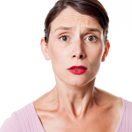 consternation: closeup portrait of fear - sad tensed young woman with tied brown hair expressing anxiety and consternation, isolated white background studio Stock Photo