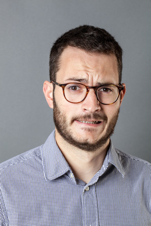 grinding teeth: portrait of fear - anxious young bearded entrepreneur with eyeglasses frowning for business stress and anxiety, grey background studio