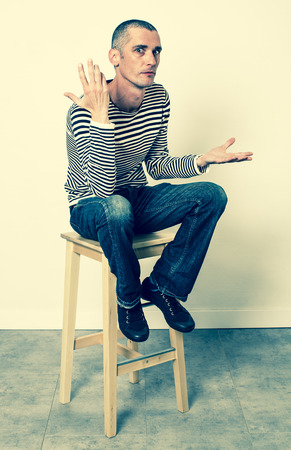 conflicted: expressive body language - complaining young man with short hair talking with his hands sitting alone on a stool, listening to problems, green effects
