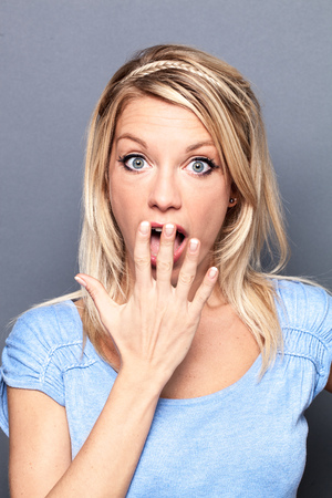 eyes wide open: surprise concept - stunned sexy young blond woman with eyes wide open hiding her mouth to express regret or mistake, grey background studio Stock Photo
