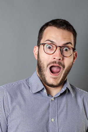 extrovert: surprise concept - happy young bearded corporate man with eyeglasses and mouth open to express amazement or having a great idea, grey background studio