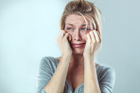 disillusioned: drama concept - disillusioned young blond woman crying with big tears expressing her disappointment and sadness, grey background studio, contrast effects Stock Photo