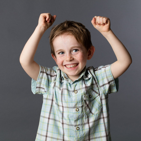 giggling: winning kid - giggling young red hair preschool child with freckles raising his arms, enjoying his winning success, grey background studio Stock Photo