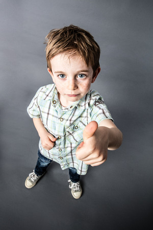 mischievous: cheeky OK - beautiful little red hair boy with freckles expressing his satisfaction, approval and mischievous success with thumbs up in the foreground with wide angle and top view, contrast effects, grey background studio