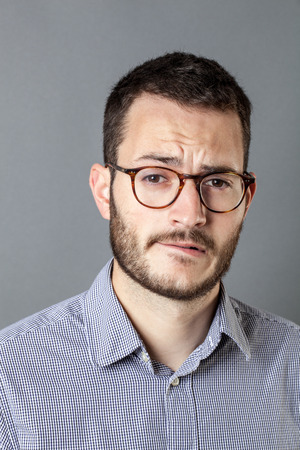 frowning: portrait of fear - thinking young bearded entrepreneur with eyeglasses frowning for business stress and anxiety, grey background studio