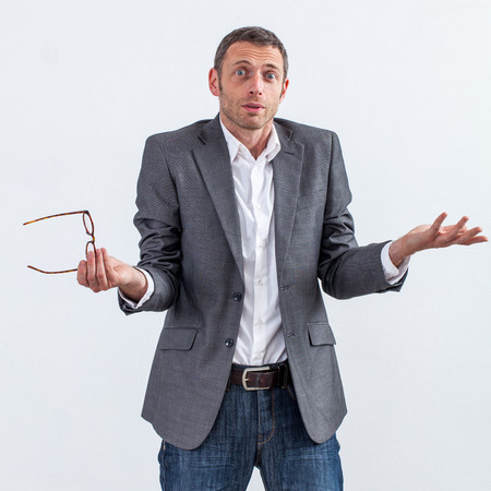 denial: corporate denial concept - surprised 40s businessman shrugging with his eyeglasses in hand having no clue about management responsibility, white background