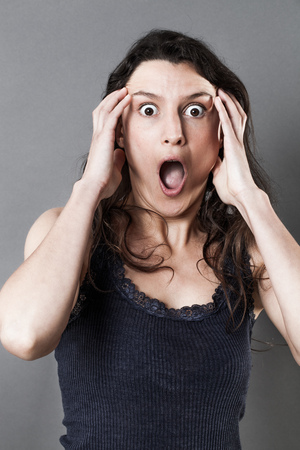 consternation: portrait of fear - offended young woman shouting, expressing jaw dropping surprise and consternation, gloomy grey background studio