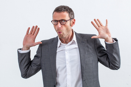 corporate denial concept - carefree 40s businessman with eyeglasses raising his hands refusing to be guilty or denying any responsibility for management fault, white background