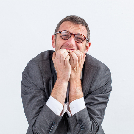 nervousness: portrait of burnout - stressed out middle aged businessman grinding teeth for nervousness and anxiety, isolated white background Stock Photo
