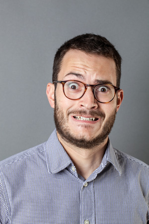 grinding teeth: portrait of fear - panicking young bearded entrepreneur with eyeglasses grinding teeth for business stress and anxiety, grey background studio Stock Photo