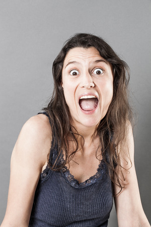 eyes wide: surprise concept - crazy young woman with long fine hair, mouth and eyes wide opened expressing amazement, grey background studio