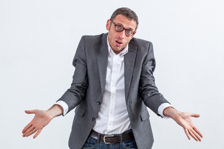 corporate denial concept - perplexed 40s businessman with eyeglasses apologizing for his management ignorance or being carefree about management confusion, white background Фото со стока