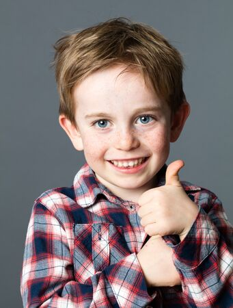 learning hand gesture - portrait of a smiling young preschool red hair boy with freckles showing his agreement with thumbs up or counting, grey background studio Banco de Imagens